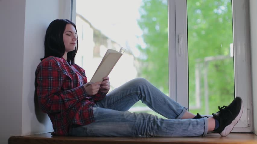 The girl reads her favorite book on the windowsill near the window in the daytime | Shutterstock HD Video #26587259