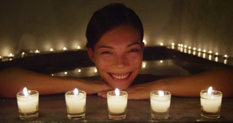 Happy smiling at camera Asian woman relaxing at spa enjoying candlelit night in hot water bath tub jacuzzi in luxury resort private hotel room. Chinese mixed race model face beauty skincare.