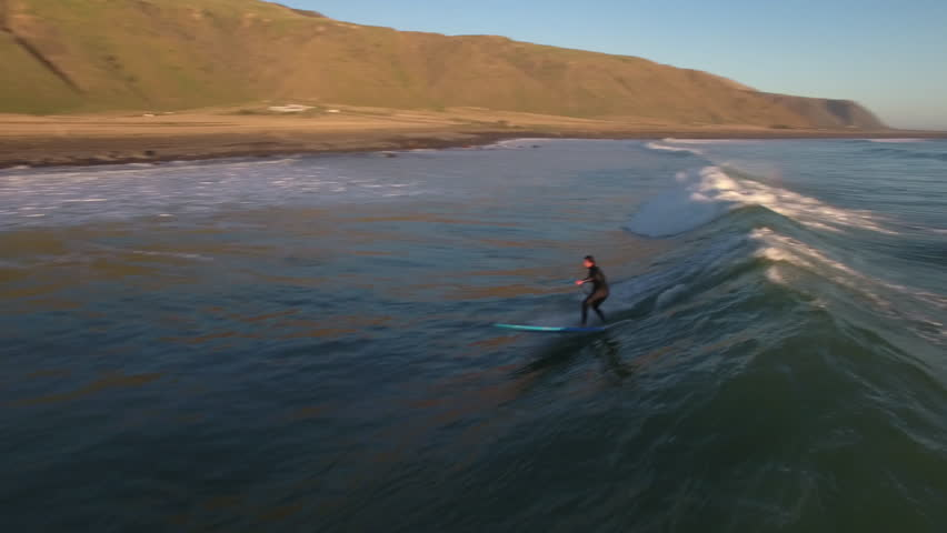 Standup paddle board surfing (SUP) a wave, aerial view New Zealand