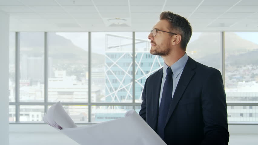 Male Architect In Modern Empty Office Looking At Plans
