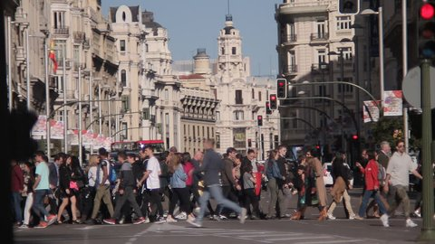 MADRID, SPAIN 01 MAY 2017: People crossing the Gran Via street to Plaza Callao in Madrid, Spain. City pedestrian traffic on a busy street in central Madrid