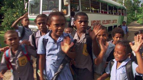 Close-up of boisterous Fijian children waving