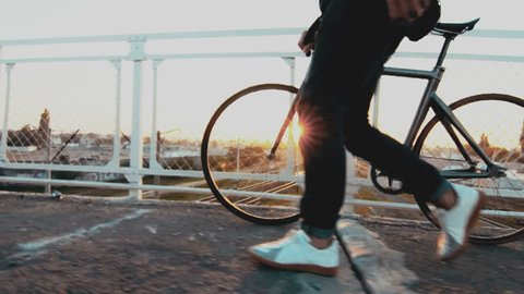 Cyclist man walking on bridge with fixed gear sport bike in sunny day