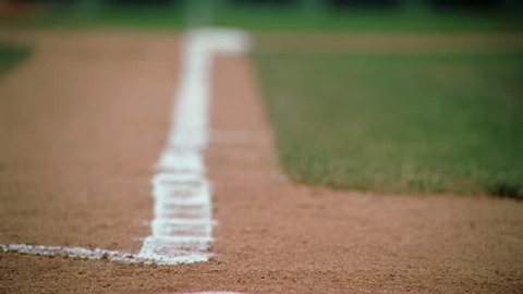 Slow-motion close-up of base runner's cleats rounding third base