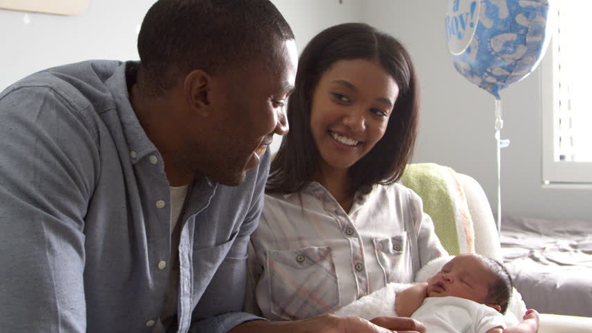 Parents Home from Hospital With Newborn Baby In Nursery