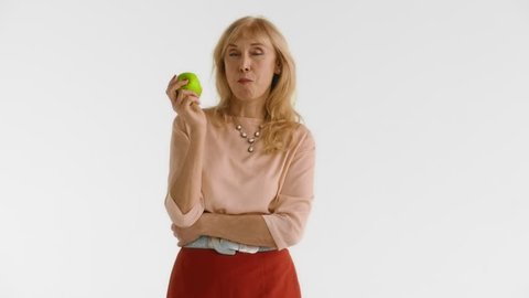 Full isolated portrait of a handsome elderly woman in a red skirt, biting a green apple standing at white background