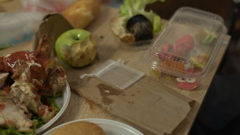 Table covered with disgusting unfinished stinky food leftovers getting spoiled