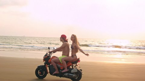 Couple riding motorcycle on the beach near the water during sunset