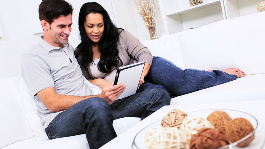Attractive young heterosexual Hispanic couple relaxing on home couch with wireless tablet