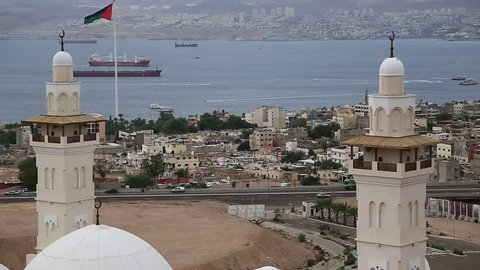 View of the Aqaba city and gulf of Aqaba in Hashemite Kingdom of Jordan and Eilat city in Israel at the distance. View from mountain in Aqaba city, Jordan. Two city and two country in one video clip