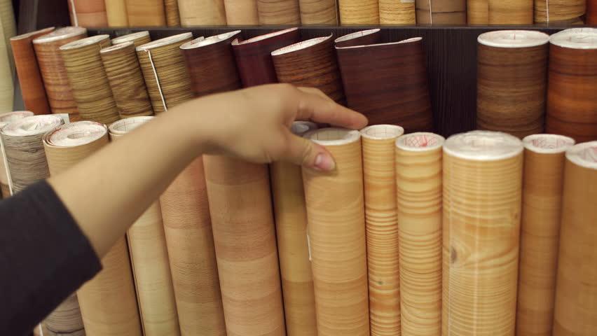 Girl looking at linoleum flooring in interior store, close-up. Racks with linoleum rolls in wholesale warehouse.