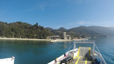 Boat approach to the Holy mount Athos in Greece. The temple on mount Athos.