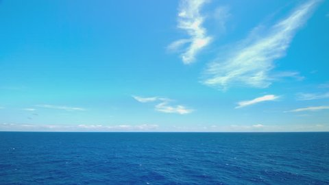 Moving Blue Oceanscape from Cruising Ship at Sea Sailing on Exotic Water with White Clouds on the Horizon during Idyllic Weather (Lower Third)