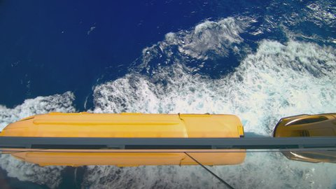 View from Cruising Ship at Sea with Yellow Lifeboats Sailing through Exotic Blue Waters with Splashing White Waves