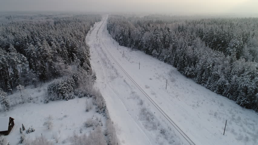 Flying over snowy forrest and railway. Train appears from bottom.