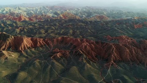 Approaching one of the most beautiful rainbow mountains in Zhangye National Geopark, part 1 of a continuous 3 part series. Aerial view on an orange sandstone mountain chain.