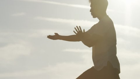 Male silhouette doing Tai Chi martial arts during sunset