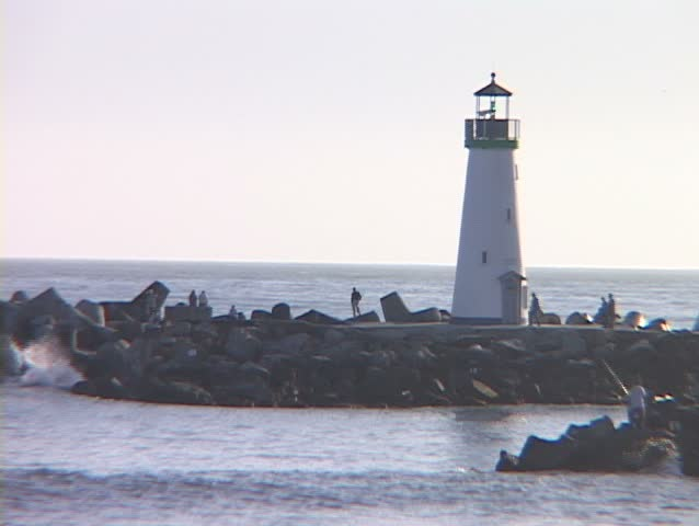 Medium shot of a lighthouse with people observing the water and a gull swooping towards the surf.