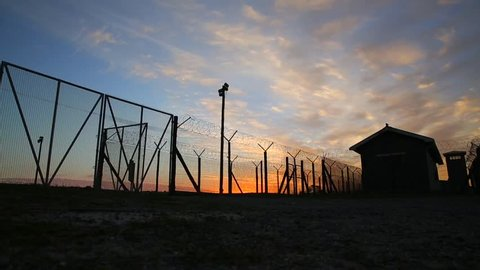 South Africa, Cape Town - May 31 2016: Robben Island Prison precinct, sunset Timelapse of sun setting and clouds moving overhead, Prison barbed wire fence silhouetted