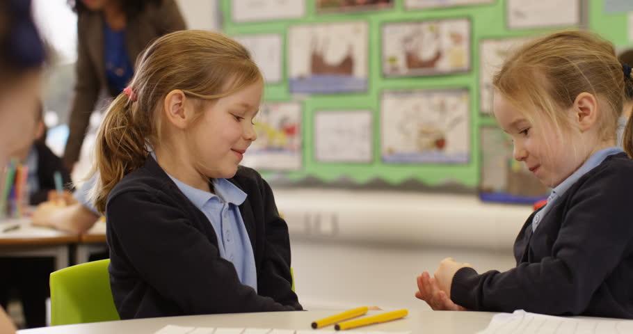 4k, Cheeky cute little girls playing rock paper scissor in a classroom. Slow motion.