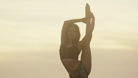 Attractive asian woman doing yoga on the beach