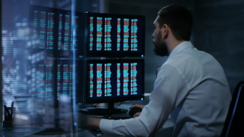 Late at Night Trader Reads Numbers on His Multiple Displays with Stock Information on Them. In Background Big City Window View. Shot on RED EPIC-W 8K Helium Cinema Camera. | Shutterstock HD Video #26897140