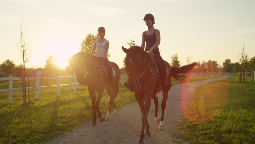 SLOW MOTION, CLOSE UP: Two cheerful young girls horseback riding amazing brown mares walking along the gravel footpath on horse ranch at magical golden light sunset. Friends on relaxing morning ride