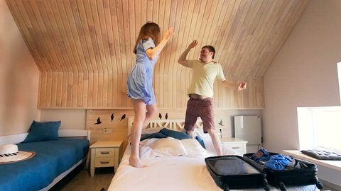 Slow motion video of young couple jumping and dancing on bed after arriving to hotel