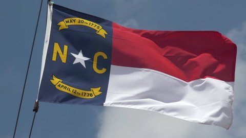 An extreme 180-fps slow motion establishing shot of the North Carolina state flag blowing in the breeze.