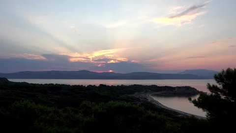 4K Timelapse of sun at sunset, sunrise over forest and sea water in Skiathos, ray light