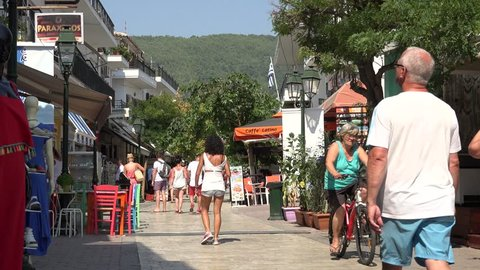 SKIATHOS ISLAND - GREECE, 5 AUGUST, 2015, 4K Tourist people shopper walk in commercial road of old town, local shops
