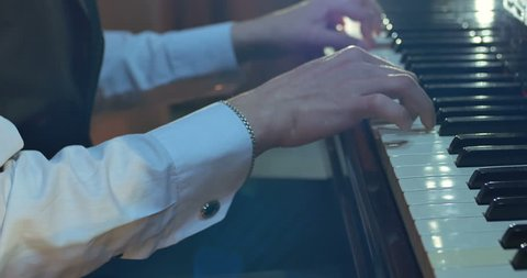 Close up of men hands playing on piano