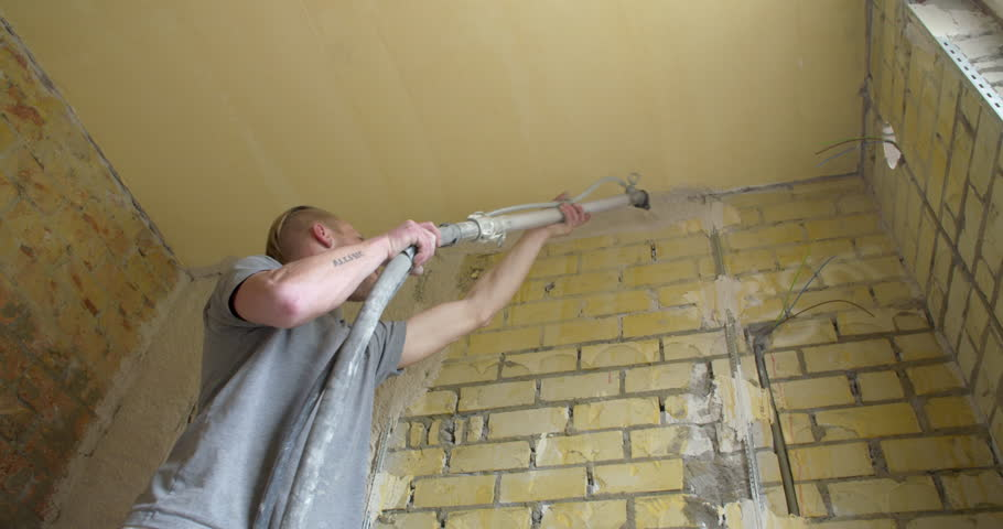 Spray On Plaster For Walls : Applying plaster to a brick wall construction worker