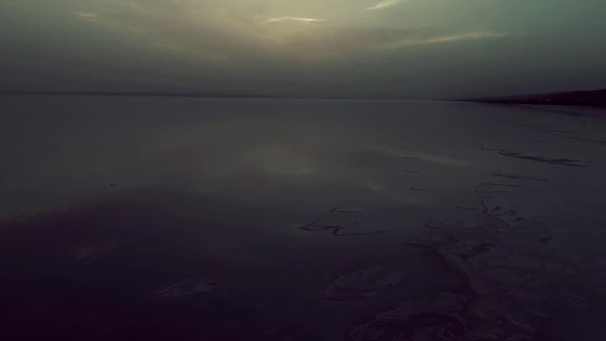 Sunset at salt lake Turkey. sunrise reflection on salt flat covered with water and clouds. night sky and dark cloud