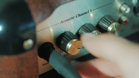 Women's hands twist tumblers on control panel of guitar amplifier. A mode switch being switches on amp. Man's hand inserts cable jack in guitar amp