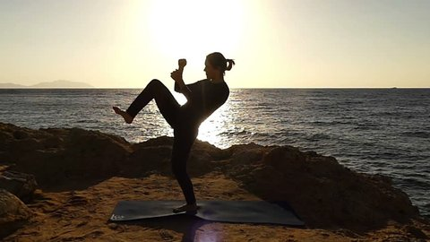 Professional Mma Girl Fighter Makes Knee Kick in Slow Motion at Sunset. Beautiful Action in the Sea Beach.
