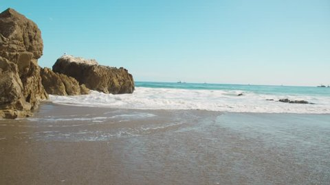 Waves wash to shore in a first person standing perspective.Gentle beautiful scenerey and reflective waves. Spring time fun for everyone at Malibu beach. Tourists may want to stop here.