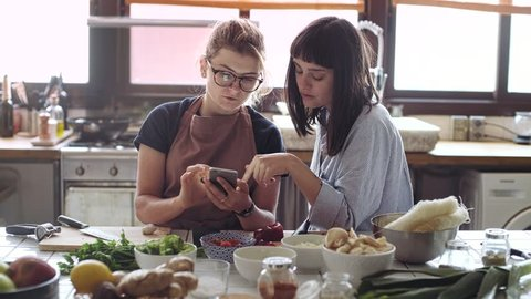 Two attractive hipster girls in casual clothing relax and chat over kitchen counter while getting ready to cook big festive meal for their family and friends from organic, fresh biologic ingredients