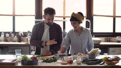 Funny happy couple cook dinner in an open space kitchen full of light, he is serious chops organic vegetables and she tries to steal a snack. they are excited, peaceful and loving