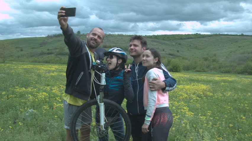 A group of happy tourists makes a selfie on a flower meadow in a beautiful field with thick clouds. Young beautiful tourists on bicycles make a joint shot on the smartphone.
