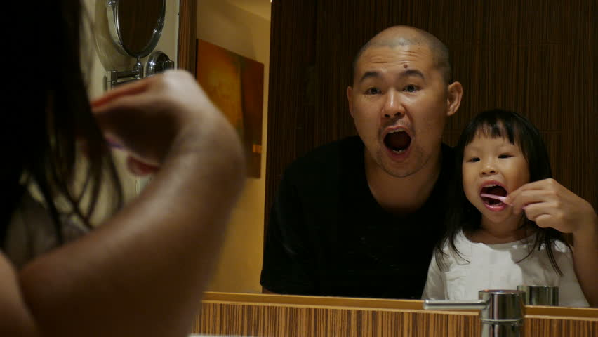 Asian father teaching his daughter to brushing her teach