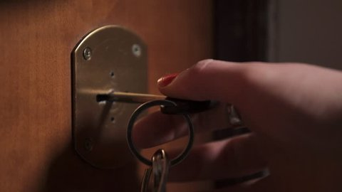 woman hands rotating the key in the lock,close up