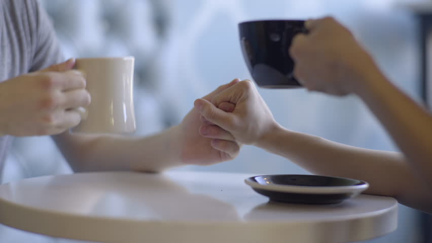 Closeup Of Cute Couple Reaching Across Table To Hold Hands, They Cheers With Their Free Hands | Shutterstock HD Video #27044716