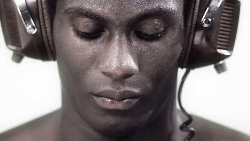 african young guy facing to the camera with a strong look with headphones in a silver style