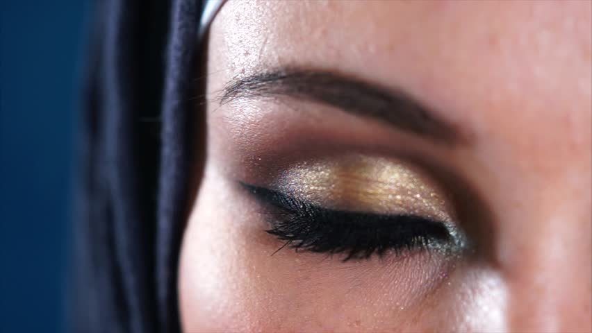 Extreme close-up of a young Middle Eastern Muslim woman in black hijab opening dark brown eyes and looking to the camera