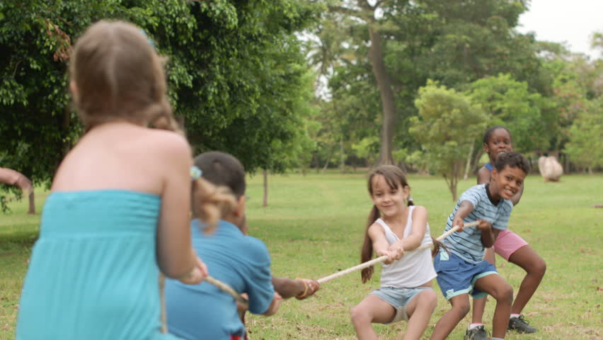 Children and recreation, group of happy multiethnic school kids playing tug-of-war in city park with teacher. Summer camp fun