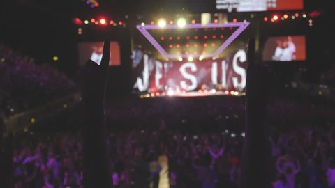 Anonymous woman with arms up at christian concert  worshiping to the God in crowd of people. Slow motion footage. Focus on hands.