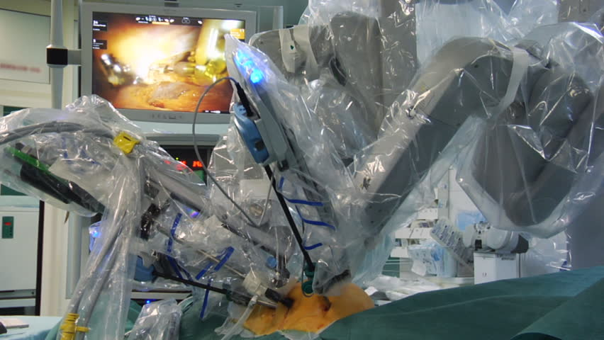 Robot performs heart surgery. Monitor shows procedure in background.