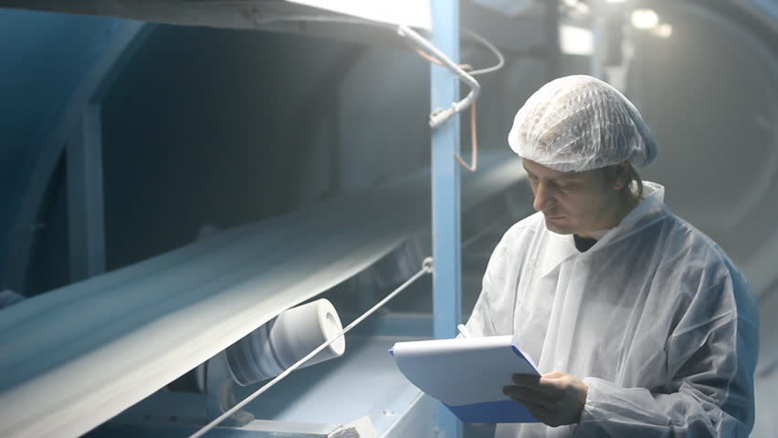 Worker controlling and writing the result of the quality of sugar on the production line