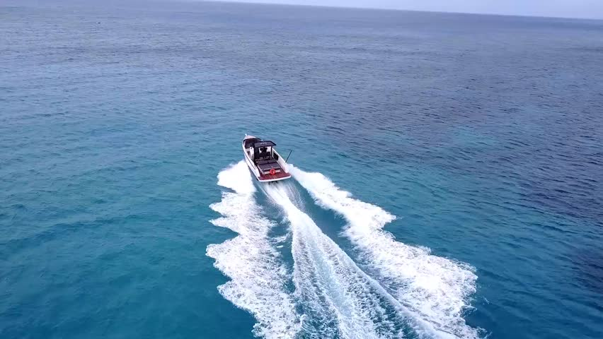 An ariel video shot by a drone of  a white speedboat/Sailboat going across the blue waters off the coast of Antigua in the Caribbean Sea with swirling water trail behind